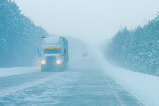 trucks on the road in a snow storm