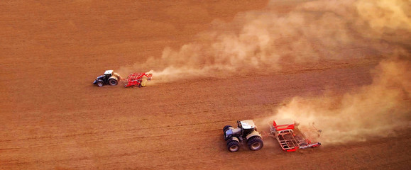aerial view of two agriculture tractors with plows. Plowing the field