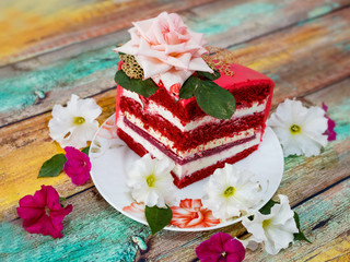 A piece of red festive cake on wooden background