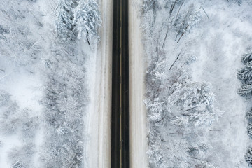 view from height, winter road with ice on the asphalt, trees under snow during the winter frost in Russia