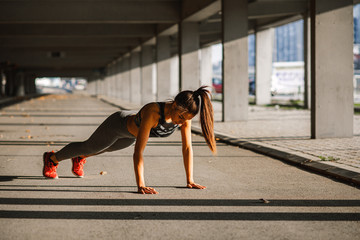 Young woman doing push ups in the urban environment