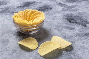 Potato chips on grey concrete table. Concept of fast food and snacks.