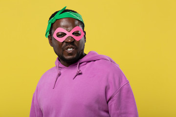 Positive delighted superhero wearing pink facial mask