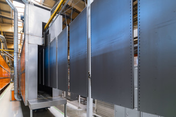 Powder coating line. Metal panels are suspended on an overhead conveyor line.