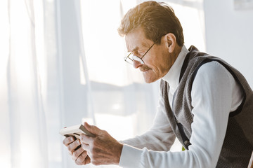 sad pensioner with mustache looking at photo in photo frame while sitting at home