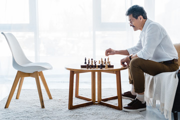senior man with mustache playing chess at home