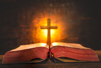 Close up Bible and cross with light of candle background on wooden table. christian concept. Wall mural