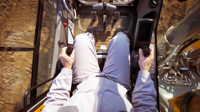The driver view, control panel of a modern bulldozer or excavator or Loader, a man in Heavy equipment machinery tractor Construction duty vehicle command cabin.