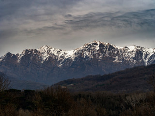 Winter evening landscape with snow on the peaks in the Apennines, Italy. View from Villafranca in Lunigana.
