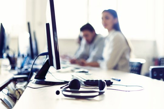 We are waiting for your call. Call center workers are working at modern office.