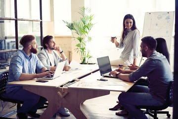 Young creative people in modern office. Group of young business people are working together with laptop, tablet, smart phone, notebook. Successful hipster team in coworking. Freelancers. Wall mural