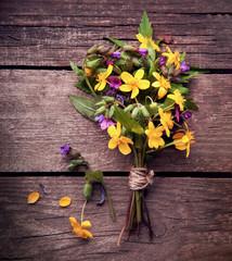 Wild flowers on old grunge wooden background
