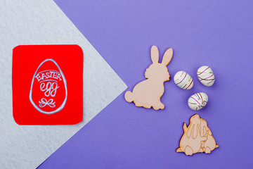 Plywood rabbit cutouts and eggs. Wooden cutout figurines of Easter rabbits and polystyrene eggs on colorful background. Red paper card with picture of Easter egg.