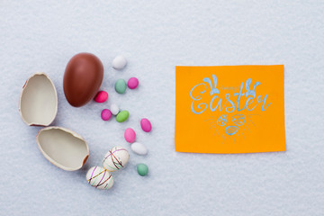 Broken chocolate egg on light background. Styrofoam Easter eggs and colorful candies. Easter greeting card. Easter present for kids.