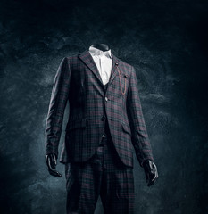Male mannequin dressed in exclusive custom made men's suit in a dark tailor studio