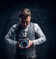 Elegantly dressed young journalist posing with a camera in a studio