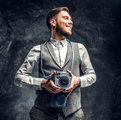Smiling elegantly dressed young journalist posing with a camera in a studio