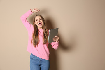 Emotional young woman with tablet celebrating victory on color background. Space for text