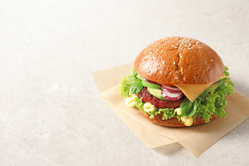 Tasty vegetarian burger with beet cutlet on light background. Space for text