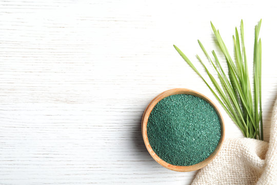 Bowl of spirulina powder, grass and napkin on white background, flat lay. Space for text