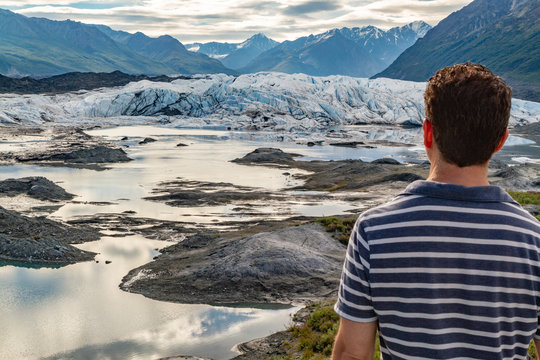 Young man gazing out at Matanuska Glacier, in Alaska, USA. Glacier surrounded by mountains and reflected in foreground pools of water.