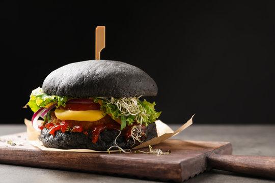 Board with tasty black vegetarian burger on table against dark background