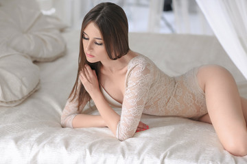 Sexy young girl in bodysuit posing in bright interior