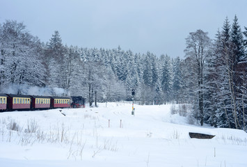 Vintage steam train crossing the Harz region in Germany in winter and snow