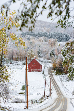 Snow covered road leading to a red barn in Stowe, Vermont, USA