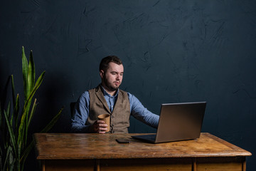 Young businessman working on his laptop on wooden table. Room for text. Dark background. Space for Text