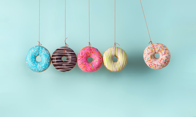 Newton's cradle from doughnuts. Collision balls made from donuts. Harm of sugar, donuts time or healthy diet concept. Dependence on flavoring, diabetes problems, weight loss.