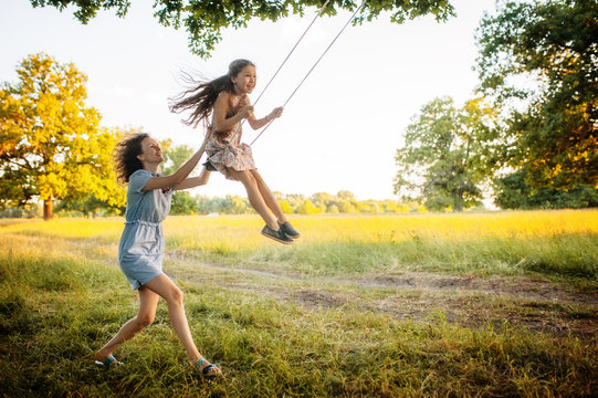 Mom swinging daughter on a swing in the field