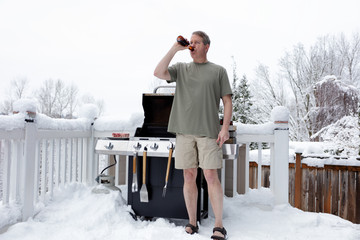 Mature man getting ready to grill while drinking beer during winter season
