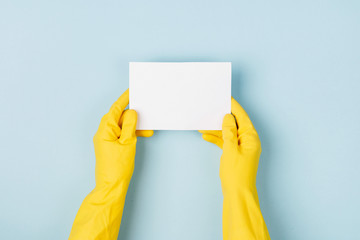Hands in yellow gloves hold empty card. Cleaning or housekeeping concept background. Copy space. Flat lay, Top view.