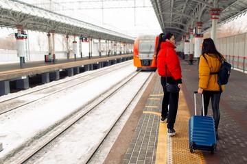 Young females walking  railway platform