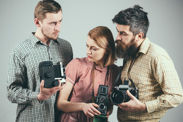 Having some problems. Group of photographers with retro cameras. Retro style woman and men hold analog photo cameras. Paparazzi or photojournalists with vintage old cameras. Photography studio