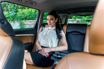 Attractive businesswoman sitting on back seat of a car