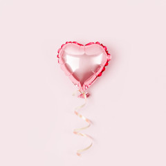 Single Balloon of heart shaped foil on pastel pink background. Love concept. Holiday celebration. Valentine's Day or wedding/bachelorette party decoration. Metallic balloon