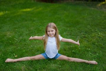 Little girl outdoor on the fresh grass do the splits