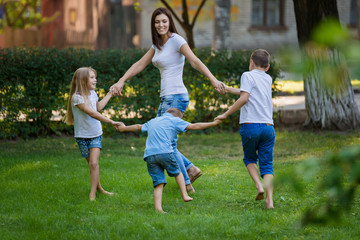 Mother and children dance on the lawn in the park