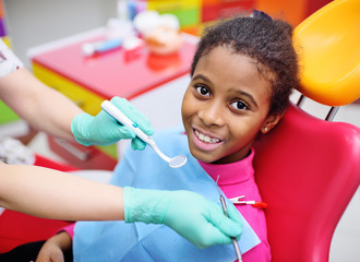 African American baby girl smiling sitting in a dental chair at the examination of the pediatric dentist.
