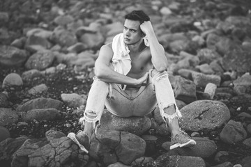 photography of young man on the stone beach