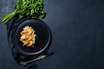 Italian risotto with shrimp on a black plate, a bunch of cilantro. Dark background, top view, space for text