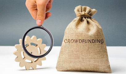 Money bag with the word crowdfunding and gear. The concept of raising funds for a crowdfunding company or a startup. Sponsoring a project. Development of new products and technologies. Donation