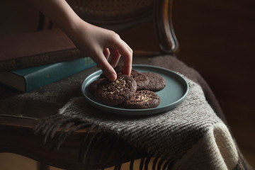 Chocolate cookies on the plate. Dark and Moody, Mystic Light food photography. Children's hand takes a cookie