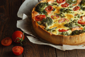 French pie Quiche or Quiche lorraine - traditional open pie with salmon, broccoli, egg, cheese, tomato. Dark and Moody, Mystic Light food photo
