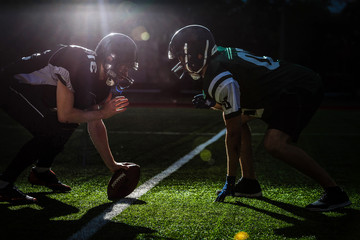 American football players are ready to start a match on modern field at night