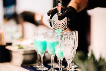 Professional bartender pouring and mixing delicious tropical blue curacao alcoholic cocktail