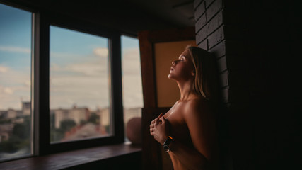 Fototapeta A hot naked blonde with closed eyes is standing in front of the window, covering her breasts with her hands. Big breasts and elements of bdsm. obraz