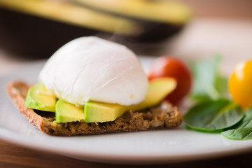 Healthy breakfast with wholemeal toast and benedict eggs with green salad and avocado